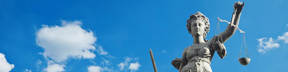 Justizia - Göttin der Gerechtigkeit vor blauem Himmel